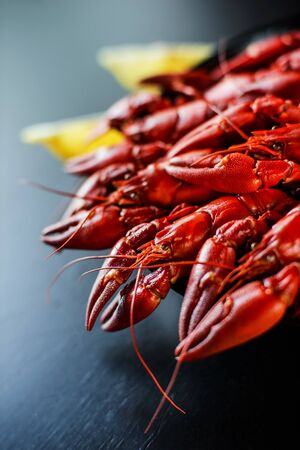 fresh hot red crawfish with lemon on dark wood table Foto de archivo