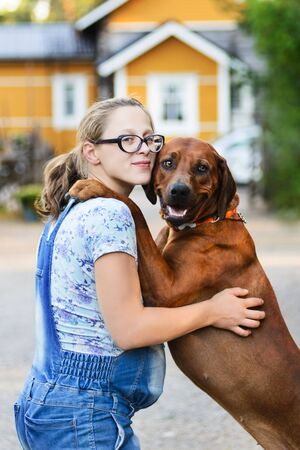 pregnant girl wearing glasses embracing and kissing dog Imagens