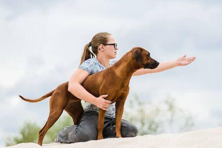 girl showing something to her rhodesian ridgeback dog