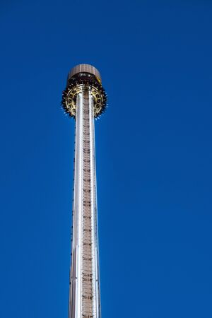 HELSINKI, FINLAND - SEPTEMBER 22, 2019:  Linnanmaki Amusement Park, people on the platform of Kingi freefall 75-metre tower ride, tallest amusement attraction in Finland (opened in 2014)