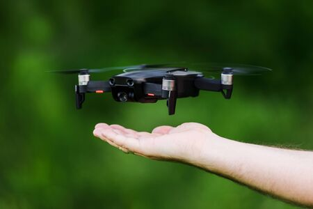 black drone floating above hand ready to land, green summer forest on background