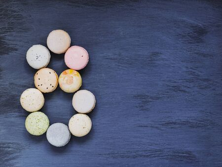 colorful pastel macaroons in form of number eight on vintage shabby dark blue violet wooden background, copy space. International women's day 8 march concept