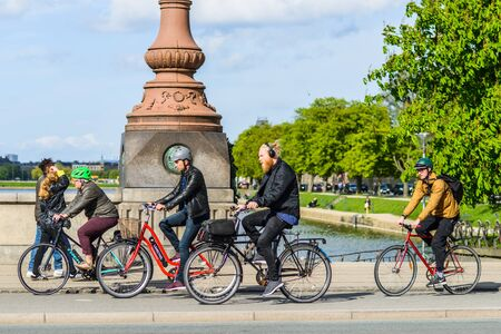 COPENHAGEN; DENMARK - MAY 03; 2018: Group of young people wearing helmets riding bicycles; crossing Queen Louise Bridge on sunny spring day; street style
