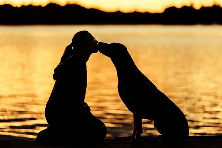Profile silhouette of girl and dog kissing in sunset light on water background, friendship concept Standard-Bild