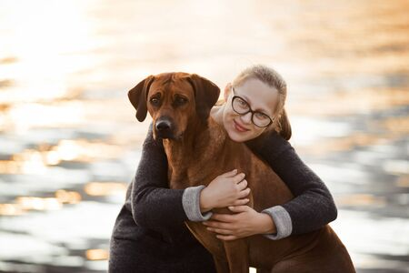 close up portrait of girl and dog hugging in sunset light on water background, friendship concept