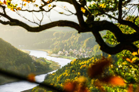 Picturesque autumn sunset scenery of Stadt Wehlen town and Elbe river from Bastei bridge and Sandstone mountains, Saxon Switzerland National Park near Dresden, Germany 免版税图像