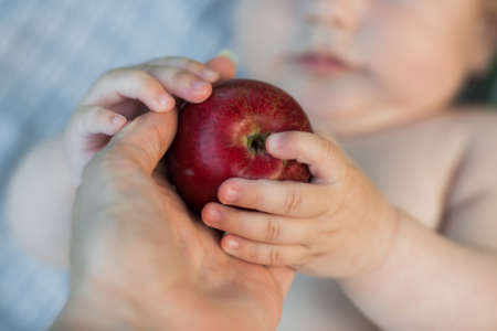 Cute baby close up hold apple close to mouth