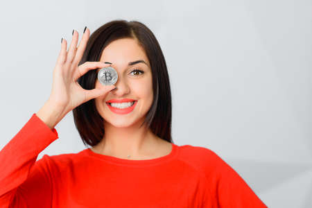 Excited smiling brunette girl wearing red holding silver bitcoin in front of her eye like an eyeglass monocle with OK ring gesture, copy space 免版税图像 - 165574450