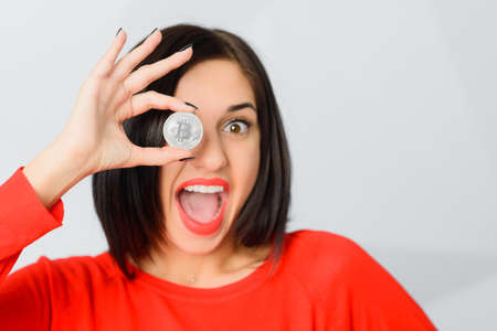 Excited smiling brunette girl wearing red holding silver bitcoin in front of her eye like an eyeglass monocle with OK ring gesture, copy space 免版税图像