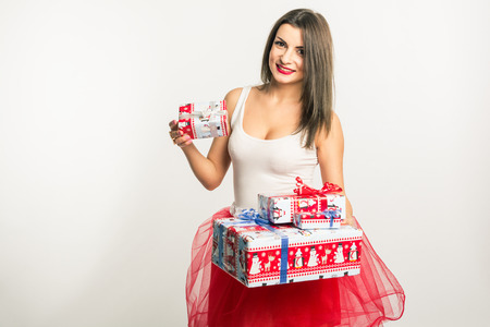 Young adorable brunette woman in a white shirt and red skirt of tulle holds (brags gives, receives) New Years gift. On a white background. Mock up. Human. New Year. Christmas. Stock Photo