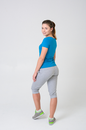 Young girl athlete in pants and t-shirt stands with her back and looks at camera