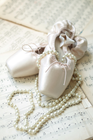 pointe shoe: Pointe shoes and pearl neclace laid on musical sheets