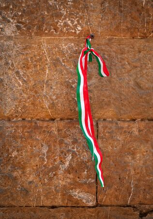 the ribbon with italian flag colors hanging on the ancient wall