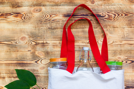 cotton bags and glass gar for free plastic shopping with wooden background