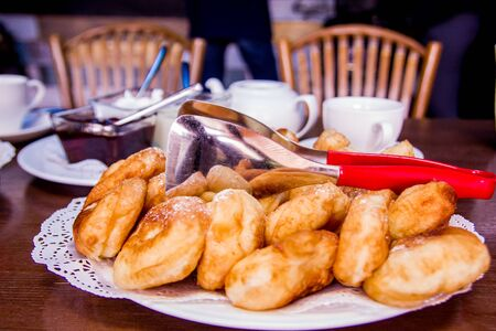 Fried pies are laid out on a plate, next to a spatula, cups, jam, sour cream, chairs. Maslenitsa. Dark background