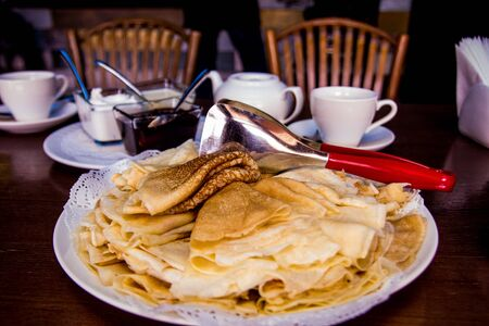 Fried pancakes are laid out on a plate with a slide, next to a shovel, cups, jam, sour cream, chairs. Maslenitsa. Dark background. Russian food