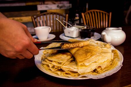 Female hand takes a pancake from a plate. Pancakes are laid out on a plate with a slide, next to a shovel, cups, jam, sour crea m, chairs. Maslenitsa. Dark background. Russian food Reklamní fotografie