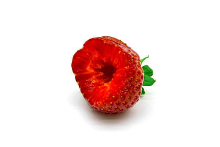 Half of a ripe juicy strawberry bitten off with teeth close up on a white background