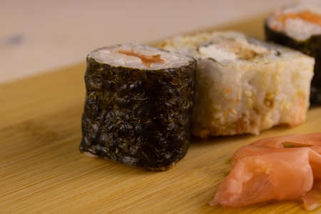 Sushi on a cutting Board with ginger, close-up.