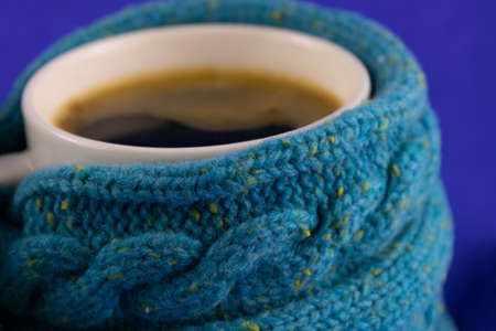 Black coffee in a warm sweater on a blue background close up
