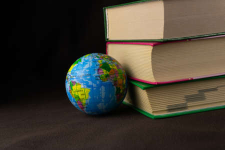 A globe and a stack of old books on a dark background