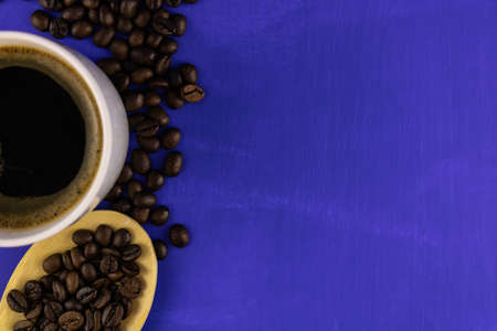 A Cup of coffee and grains in a wooden spoon on a blue background. Copy space, top view.