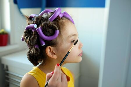 a little girl pretends to be an adult woman with curlers in her hair holds eyebrow brush looks in the mirror. The concept of kids pretending to be adults