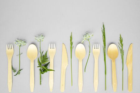 disposable wooden forks, spoons and knives with summer herbs on light blue background. eco friendly. no environmental pollution, no plastic.