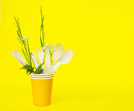 disposable wooden forks, spoons and knives in a paper cup on yellow background. eco friendly. no environmental pollution, no plastic.
