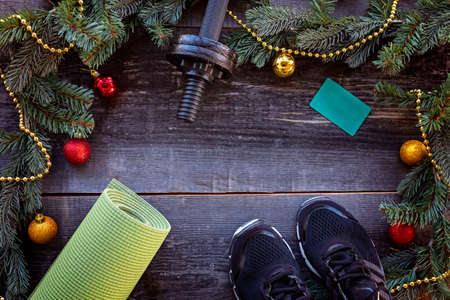 Christmas and Happy new year background with dumbbells, yoga mat, sneakers, branches fir tree glass balls and bows bells on white background. Copy space. Flat lay, top view. Stock Photo