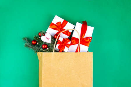 Kraft paper bag on green background. With gift boxes, spruce branches and christmas decoration. Black friday christmas gift preparation concept.
