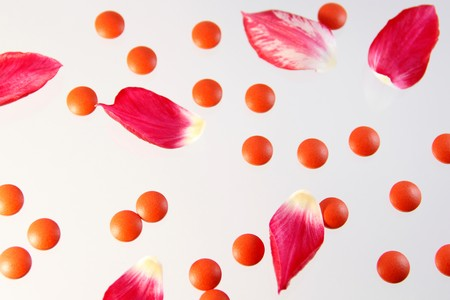 pills and tulip petals on white background