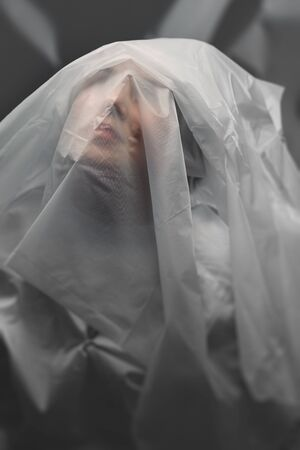 The female face is covered with white translucent cellophane. Quarantine.