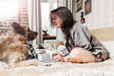 Attractive smiling young woman working at home on a laptop. Nearby lies a dog.