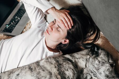A young woman is lying on a bed with two dogs. Archivio Fotografico