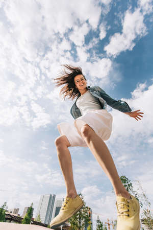 Beautiful woman jumps high up. She flies swiftly against the sky, joyful and happy. Stock Photo