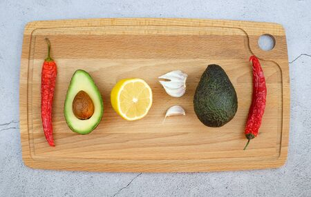 Ingredients for mexican sauce guacamole. Avocado red hot peppers garlic lemon. Wooden cutting board. Top view.