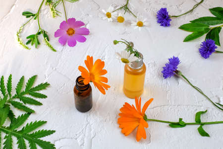 Bottles with natural oil and flowers on white background as aromatherapy concept Imagens