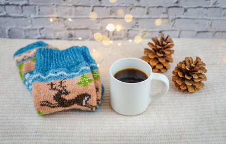 Christmas socks, mug of coffee, pine cones and golden bokeh on white bricks background. Winter holiday christmas and new year concept. 版權商用圖片