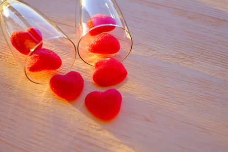 Marmalade red hearts and two glasses of champange on the wooden table close-up. Abstract romantic background. Selective focus