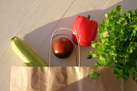 Fresh vegetables in grocery eco bag on wooden background, sunlight, top view.
