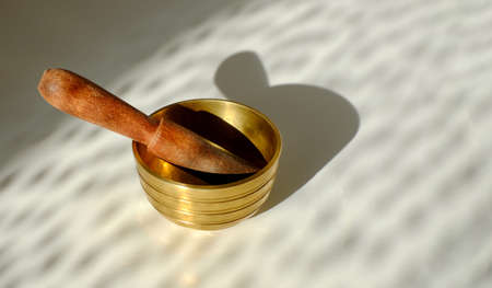Tibetian singing bowl on white background with shadows and sunlight. Sound therapy, relaxing. Copy space.