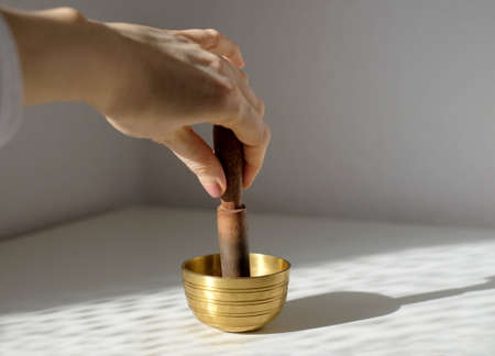Hand playing on a tibetian singing bowl on gray background, copy space.