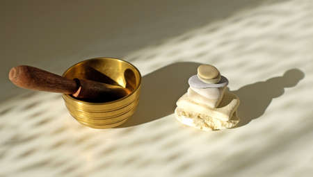 Tibetian singing bowl and stone pyramid on the table, abstract shadows and sunlight. Relaxation concept.
