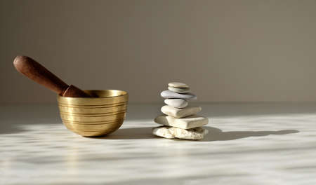 Tibetian singing bowl and stone pyramid on the table on gray background, relaxing idea, with copy space.