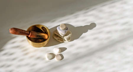 Tibetian singing bowl, stone pyramid, stones, with sunlight abstract background, relaxing concept. Top view, copy space.