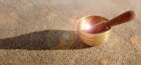 Himalayan tibetian singing bowl on sand with sunlight, bokeh. Harmony and relaxation concept. Copy space.