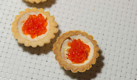 tartlets with butter and red caviar on a white background, a delicious treat for the holiday