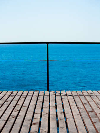 placidity: Weathered wooden platform against a background of blue sea and sky in a minimalist style