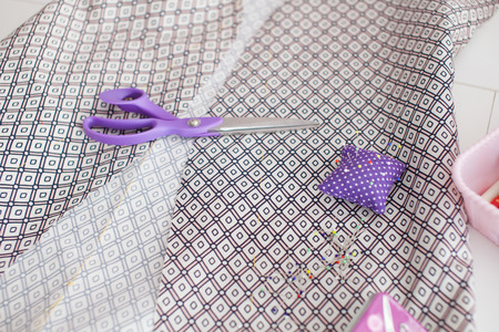 Sewing textile or cloth. Scissors pin cushion, and natural fabric. Work table of a tailor. Shallow depth of field.